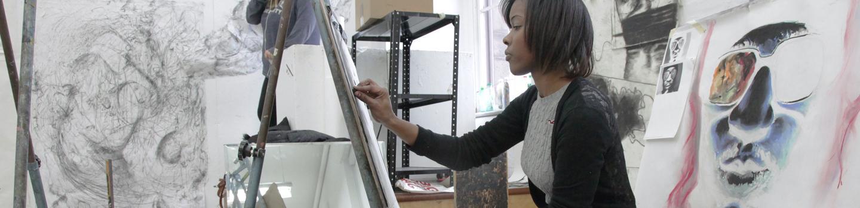 Student drawing in art studio.