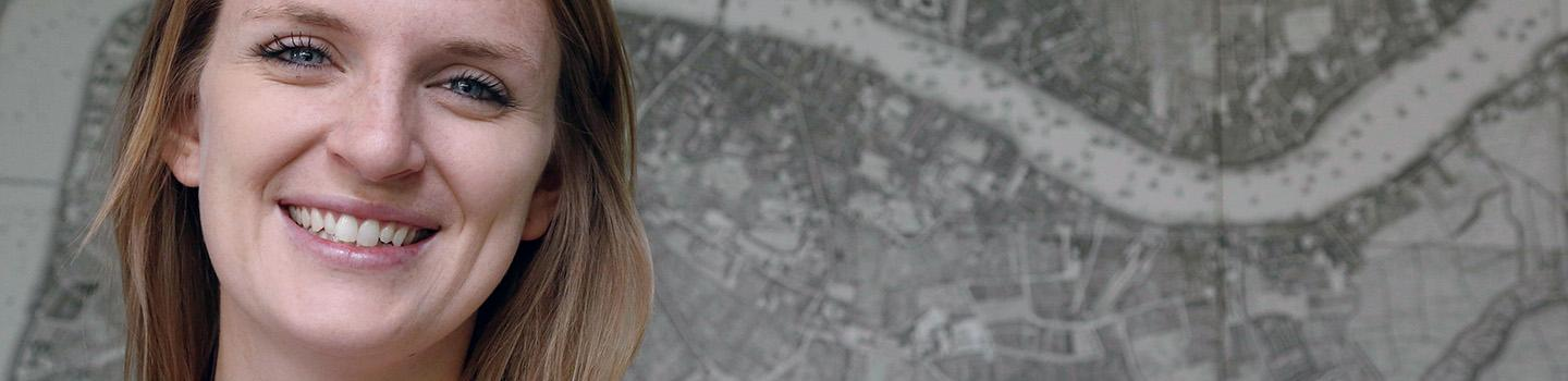 a woman stands in fromt of a wall map
