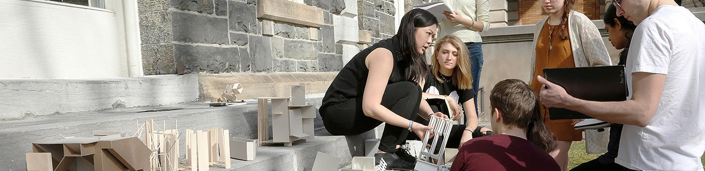 six people sit on stone steps outside a building and look at small architectural models