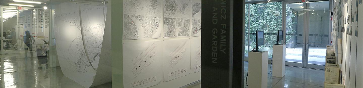 Angled view of sectional walls within an art gallery with mechanical drawings, to LCD displays, and a black pillar in the center