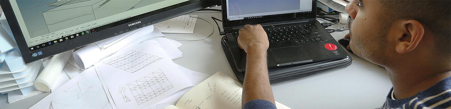 A man using a laptop with a computer screen and drawings on the desk