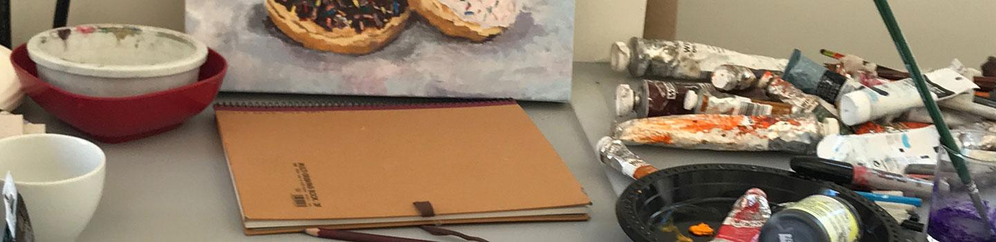 table with close-up of oil paint tubes, a notebook, bowls and the bottom of a canvas with doughnuts painted.