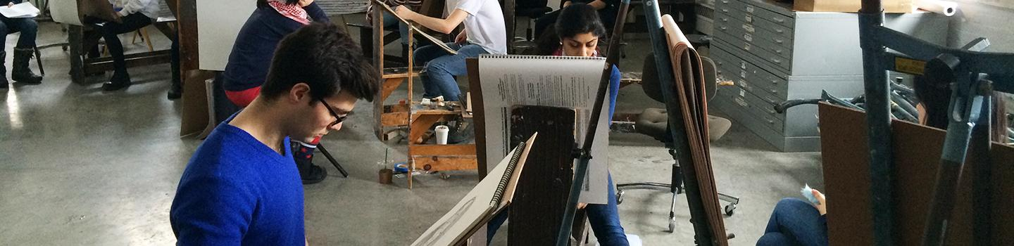 people painting on easels in a studio