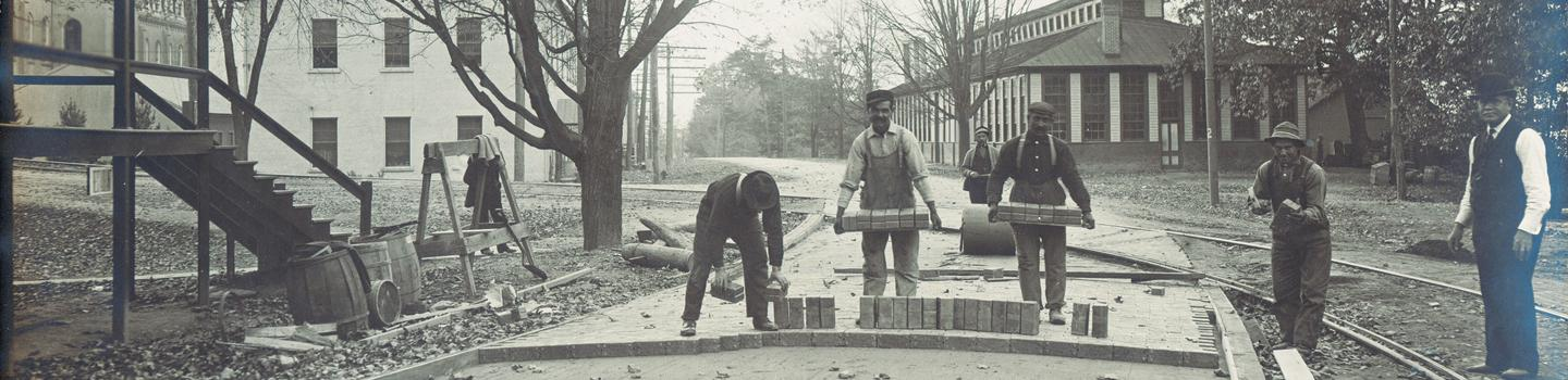 Black and white photo of men laying first bricks for building construction