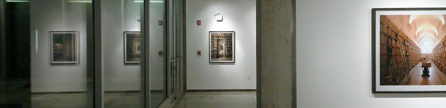 View of a gallery with photos of books and a view of the outside with snow on some stairs