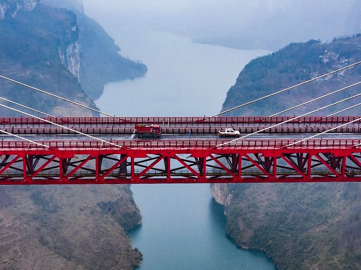 A red girder-and-cable bridge spans a deep canyon and a river.