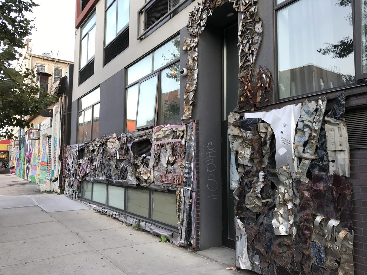A building covered in scraps of metal containing graffiti and stickers.