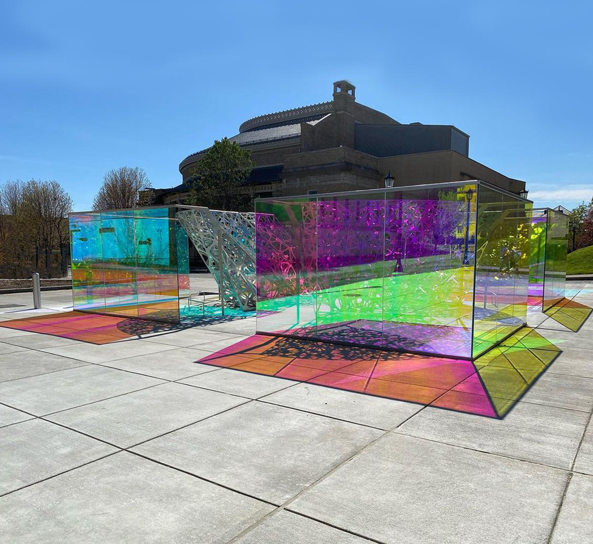 Multicolored glass boxes reflecting multicolored light onto concrete.