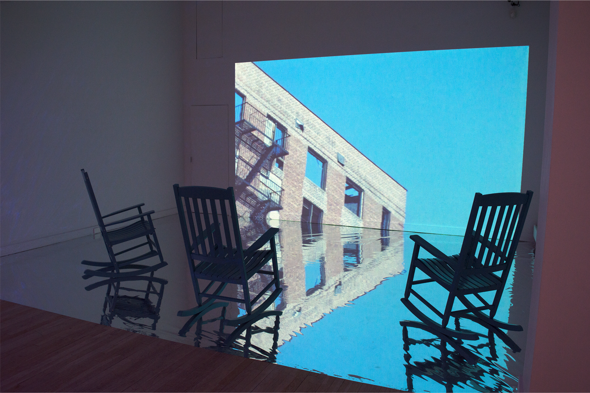 Three blue chairs sitting in front of a projected image on the wall.