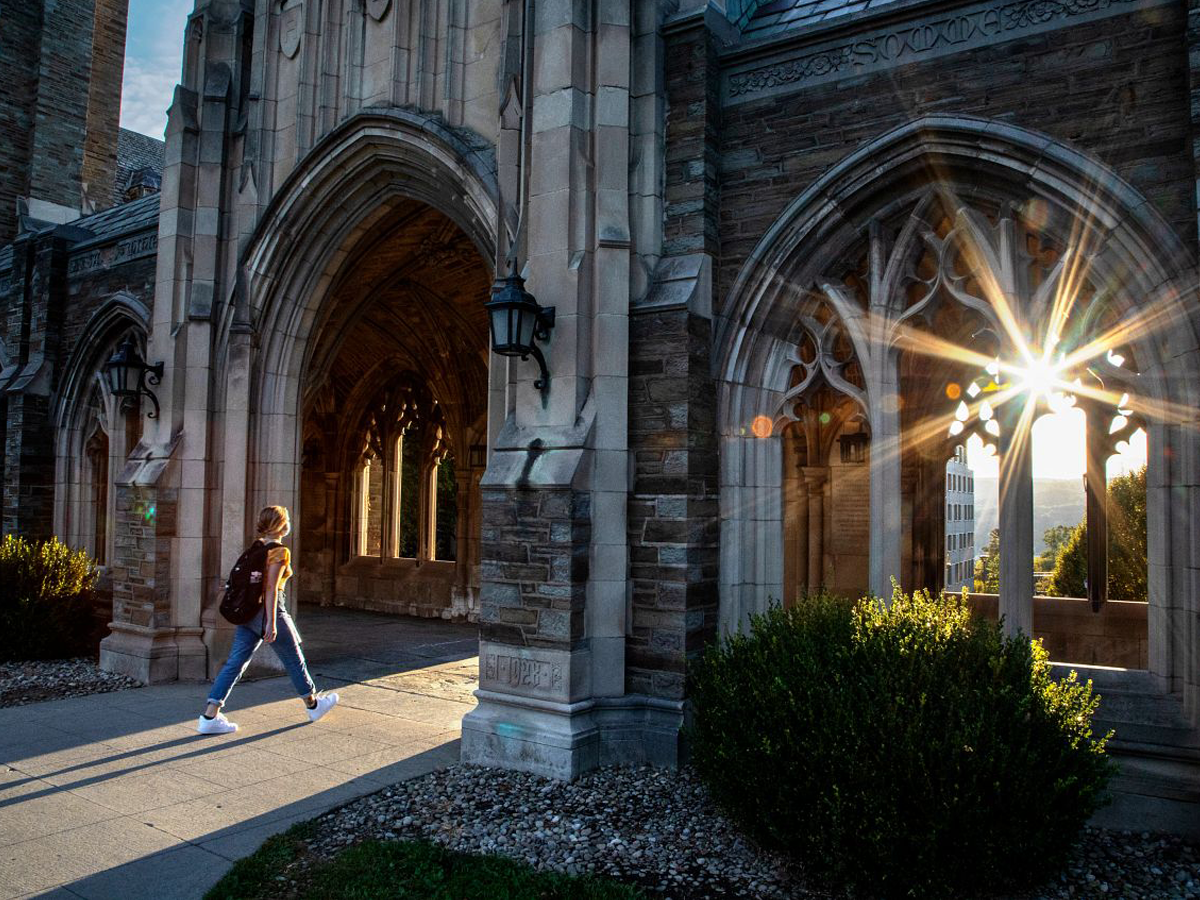 A person walking into an archway with a sunlit lens flair peeking through.