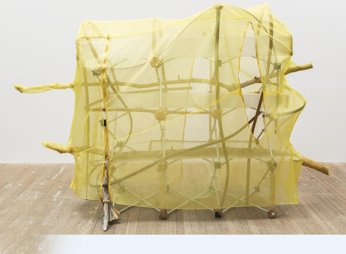 sculpture of sticks and cloth draped in yellow