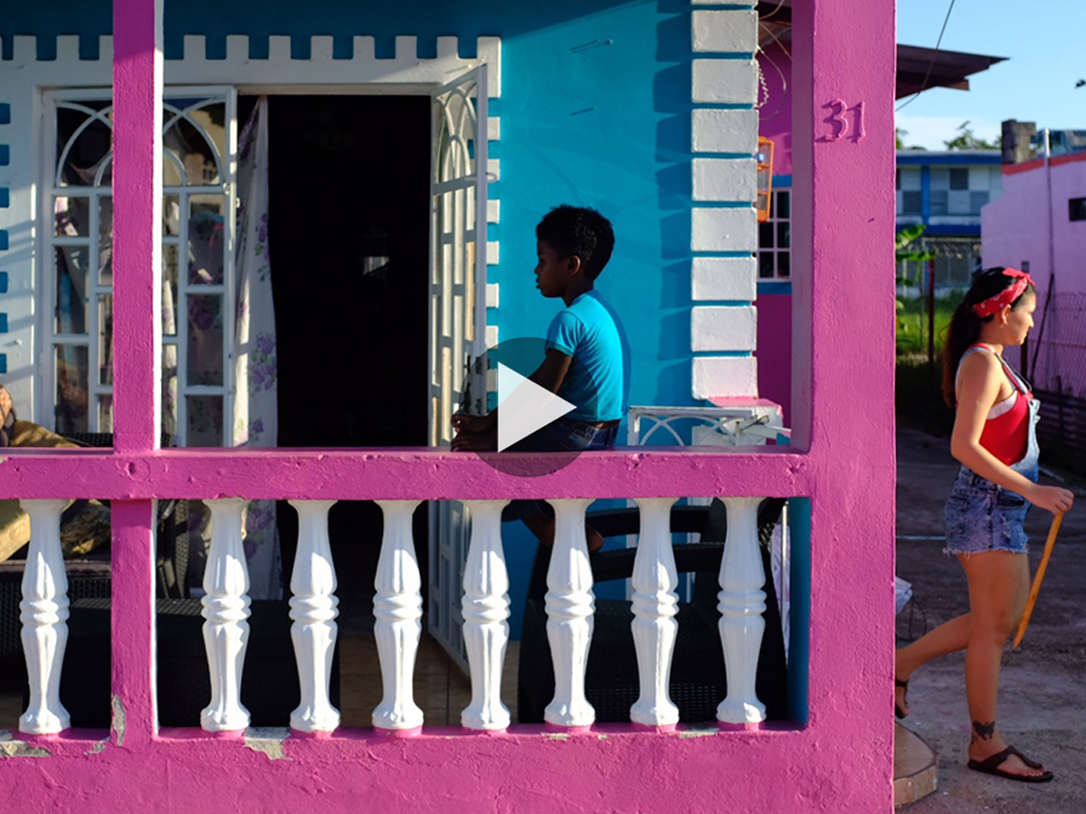 A boy sitting on a blue and pink house porch with a woman walking away.