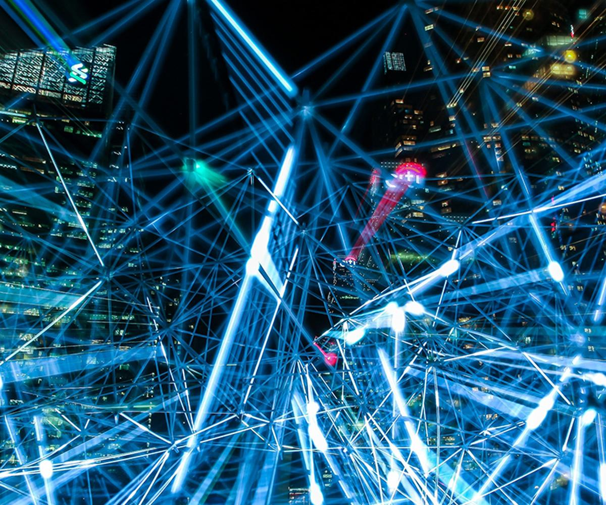 Blue glowing lines of light in a web, over a cityscape at night.