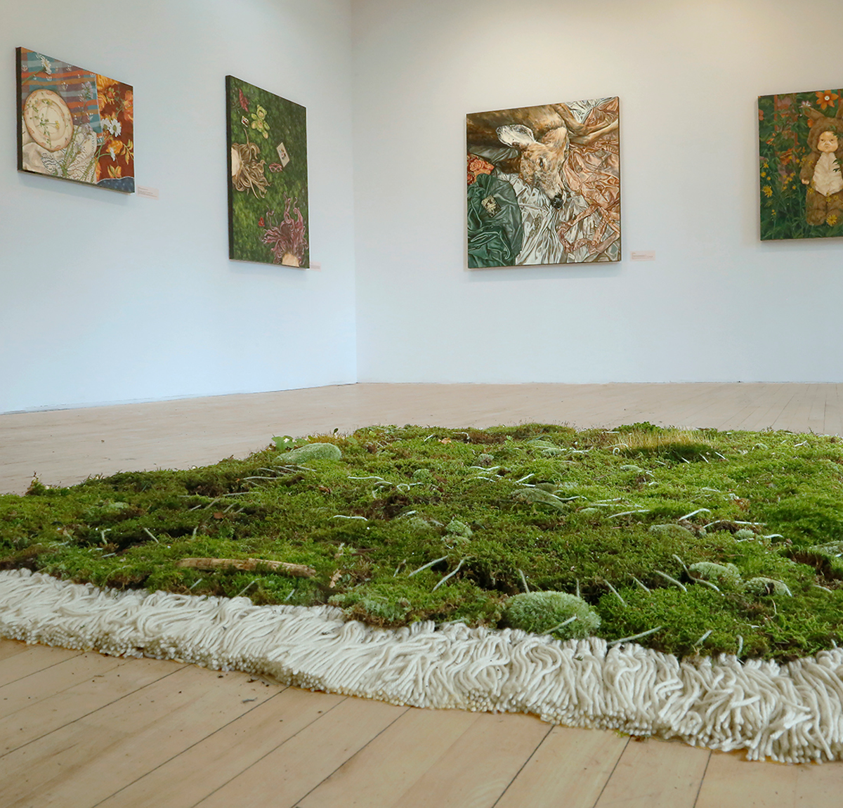 A green and white rug on a light wood floor with painting hanging on the wall in the room.