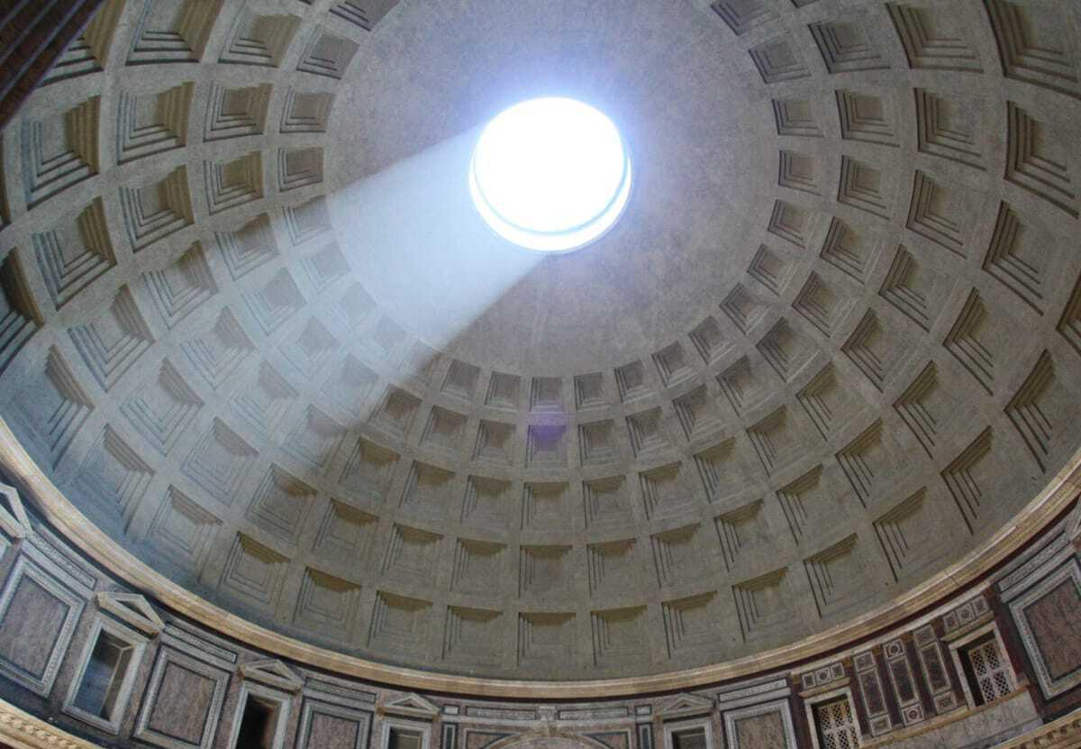 an image of a domed ceiling of the Pantheon with a hole in the middle with light breaking through and text on top