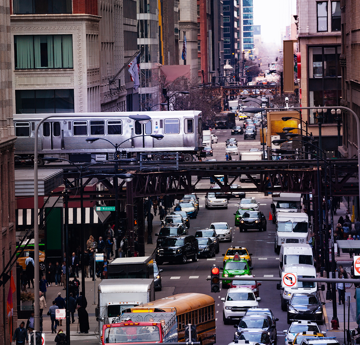 A congested city with trains, cars, and people surrounded by buildings.