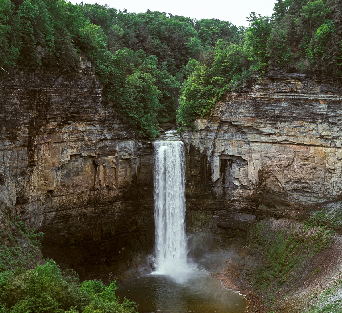A large waterfall in a valley surrounded by trees.