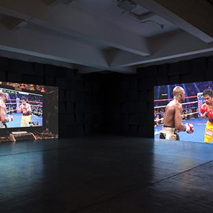 A dark room with two large screens with different projections of a boxing match on them.