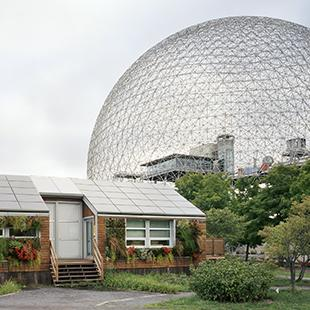 Montreal world's fair globe in the background of a suburban house with solar panels and plants flowing from its façade