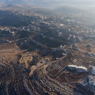 An aerial photograph of landscape and buildings including the Palestinian Museum in the lower right hand corner