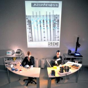Two people sitting at semicircular desks in front of a projected image of DNA.