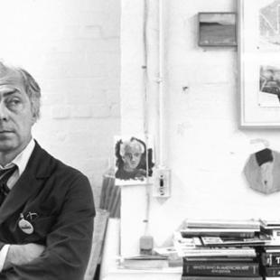 Middle-age man iwearing a smock in an art studio.