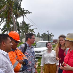 Nine men and women talk together with a white car and palm trees in the background