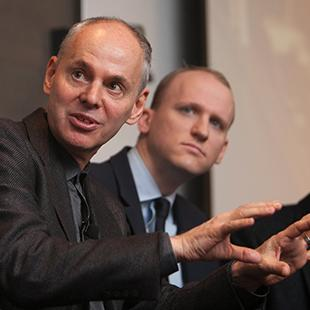 three men in a row wearing black jackets, one of them looking past the camera and gesturing with his hands