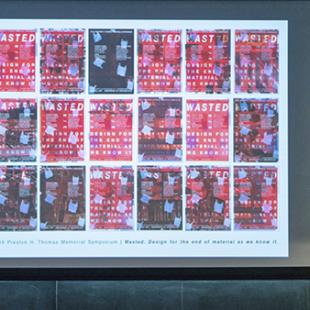 A grid of 18 red and gray posters projected on a very large projection screen