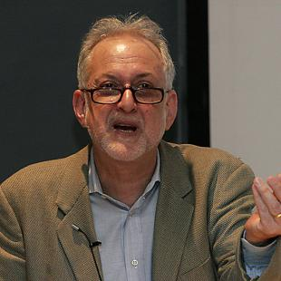 Man with gray hair, beard, and glasses speaking and gesturing with one hand