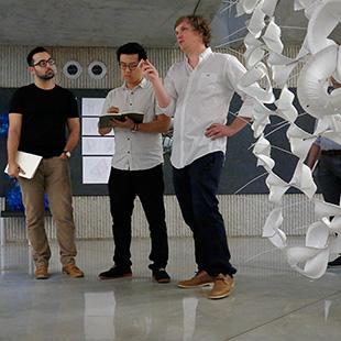 Four people stand between suspended chains of white fabric