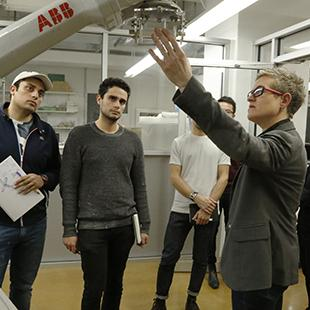 a group of students and faculty discussing a robotic arm