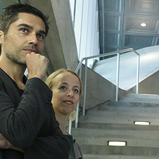 A mand and woman standing in front of a concrete staircase looking beyond the camera