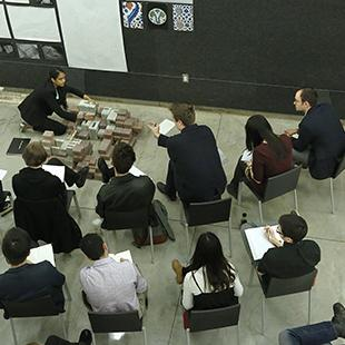 Students and faculty seated in chairs examine an architectural model