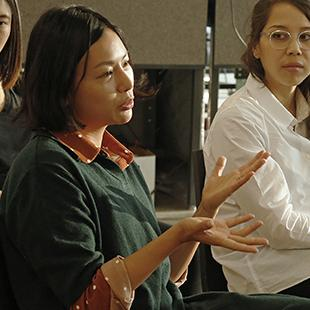 Women seated in a classroom as one speaks and gestures
