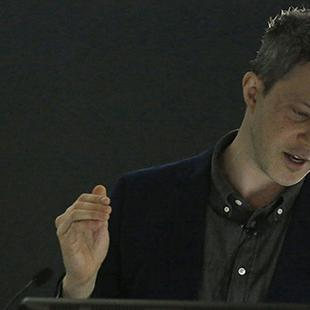Man lecturing at podium against a black background
