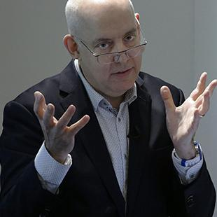 a man wearing eyeglasses with hands splayed speaks into a microphone