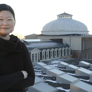 woman on a roof with a white dome and skylights in the background