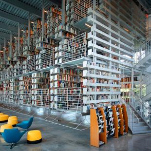 Vertical stacks of books suspended from a ceiling in a warehouse-sized space