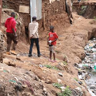 people in a global south settlement with sewage and trash in the water behind them