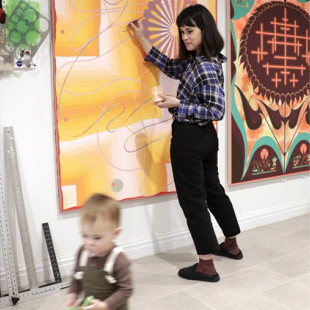 A person painting on a colorful hanging and a child walking away.