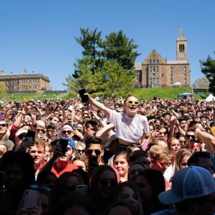 a throng of young people waving arms and cell phones in the sunshine with two stone buildings on the crest of a hill behind them