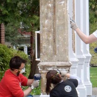 Three people in t-shirts scraping paint on a column