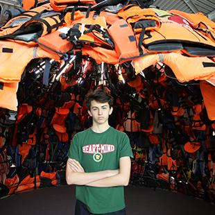 man stands with arms crossed in the opening of al large igloo made of colorful life jackets