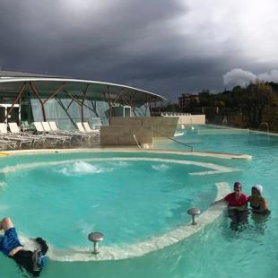 Three poeple in a tourquoise swimming pool under a arched canopy and dark sky