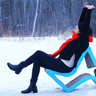 Woman with her arms raised seated in a blue star-shaped chair in the snow