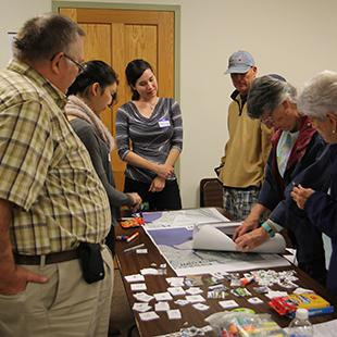 group of people standing looking at maps that lay on a table in a room