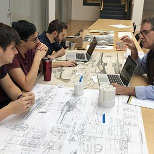 Men at a table examine diagrams and models of gun components