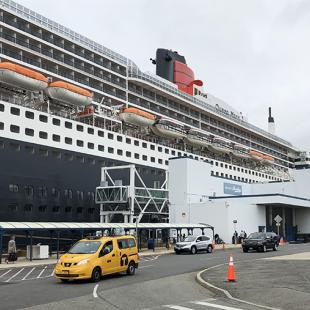 tall cruise ship docked at a city port terminal with taxi cab and cars in front
