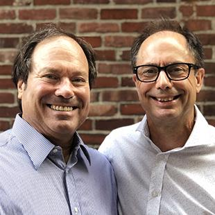 two men standing in front of a brick wall